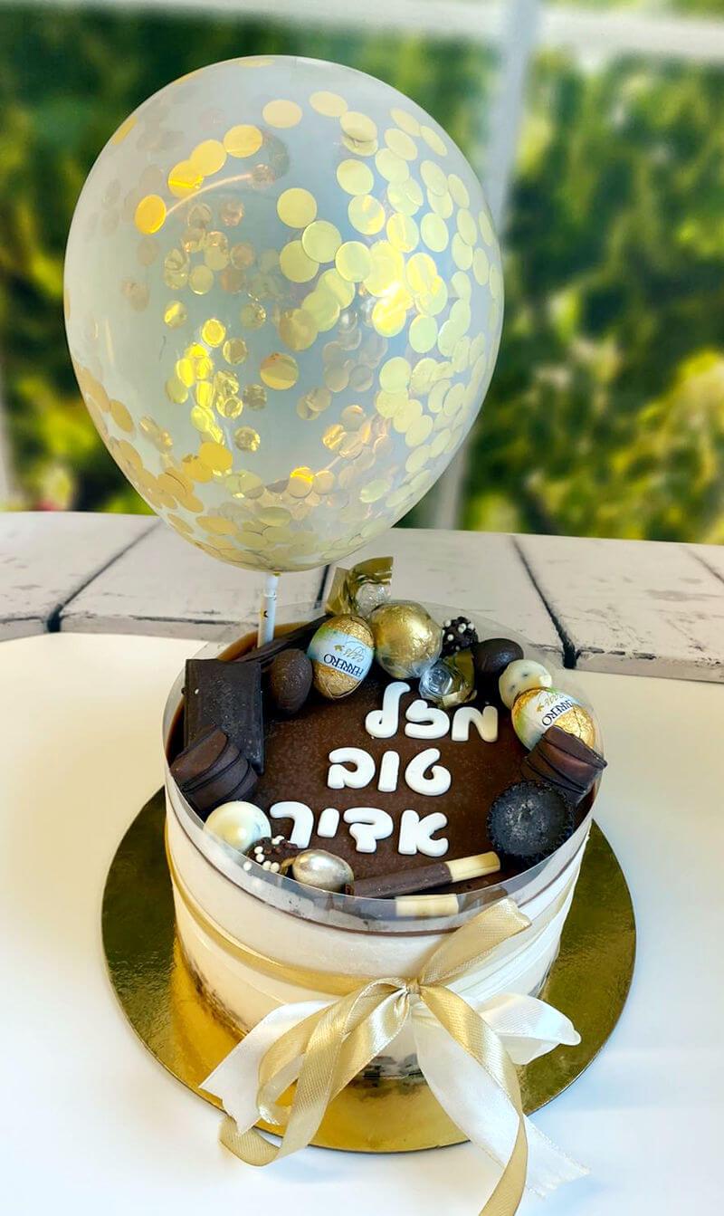 עוגת מוס קינדר בואנו מעוצבת עם ממתקים ובלון